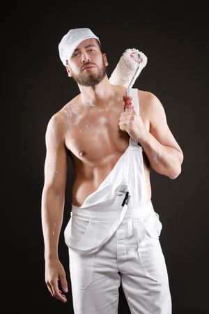 Attractive bearded young painter in white dungarees, hat and standing bare chest with paint roller, on a gray background