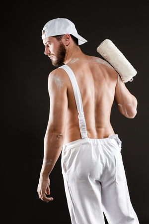 bare chest: Attractive bearded young painter in white dungarees, hat and bare chest standing back with paint roller, on a gray background Stock Photo