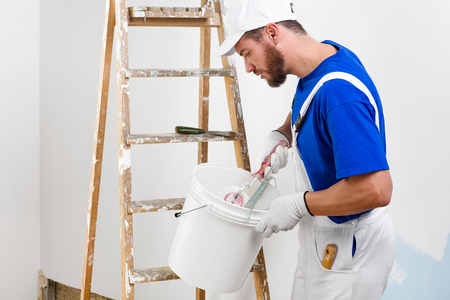 dungarees: Handsome young painter in white dungarees, blue t-shirt, cap and gloves takes color with brush roller from the bucket Stock Photo