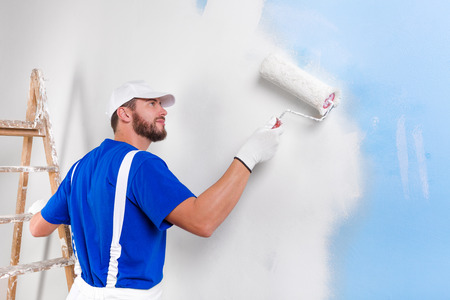 Portrait of handsome young painter in white dungarees, blue t-shirt, cap and gloves painting a wall with paint roller. Stock Photo