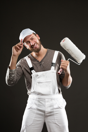 qualified worker: Attractive bearded young painter in dungarees and white hat standing with paint roller, looking at the camera on a gray background