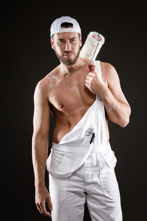 bare chest: Attractive bearded young painter in white dungarees, hat and standing bare chest with paint roller, on a gray background