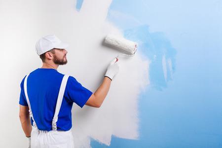 pintor de casas: Vista posterior del apuesto joven pintor con mono blanco, camiseta azul, gorra y guantes de pintura de una pared con el rodillo de pintura.