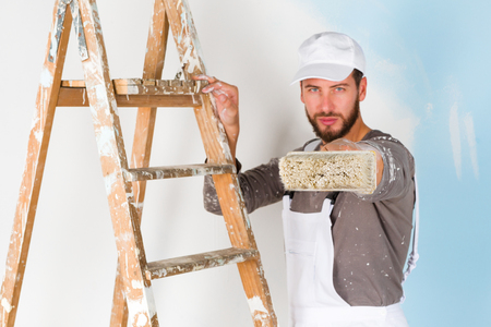 splattered: Portrait of handsome young painter in white dungarees, splattered shirt and cap, leaning on a vintage ladder aiming a paint brush