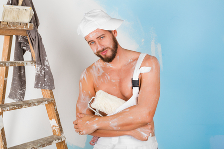 bare chest: Portrait of funny bare chest paint-splattered painter with cap, paint roller and vintage ladder, smiling and looking at camera Stock Photo