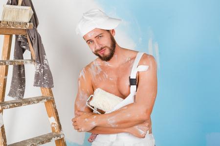 nackte brust: Portrait of funny nackte Brust lack bespritzt Maler mit Kappe, Farbroller und Vintage-Leiter, lächelnd und Blick in die Kamera