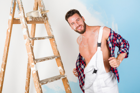 painter: Portrait of handsome bare chest paint-splattered painter with vintage ladder, undressing and looking at camera