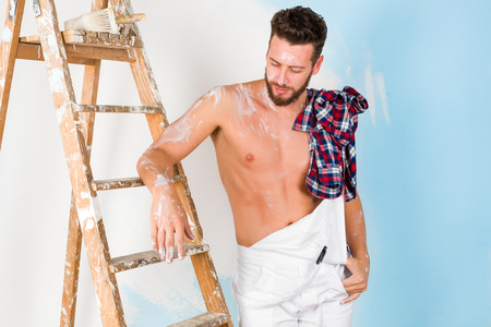 unbuttoned: Portrait of handsome pensive bare chest paint-splattered painter with vintage ladder, looking down