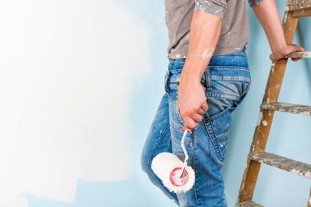HOMBRE PINTANDO: Pintor pintura en la camisa salpicada de pintura de una pared con el rodillo de pintura y apoyado en una escalera de madera