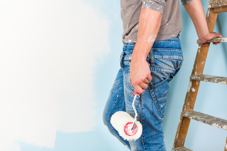 Painter in paint splattered shirt painting a wall with paint roller and leaning on a wooden ladder Stockfoto