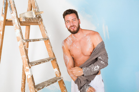undressing: Portrait of handsome seductive paint-splattered painter with vintage ladder, undressing and looking at camera