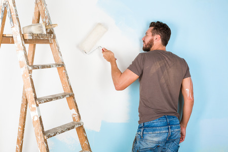 Portrait of handsome young painter in paint splattered shirt painting a wall with paint roller