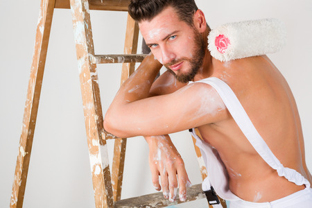 bare chest: Portrait of seductive bare chest paint-splattered painter with paint roller and vintage ladder, posing and looking at camera