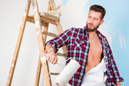 Low angle portrait of handsome pensive painter with open shirt, paint roller and vintage ladder, posing and looking aside Stok Fotoğraf