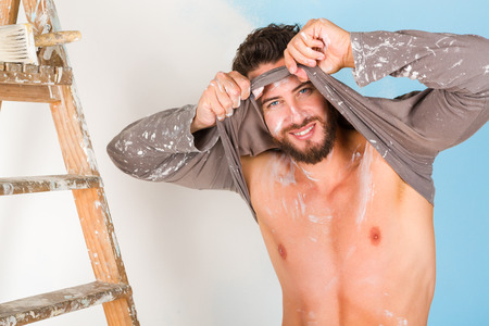 undressing: Portrait of handsome sexy paint-splattered painter with vintage ladder, smiling while undressing and looking at camera