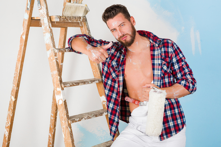 unbuttoned: Portrait of handsome painter with unbuttoned shirt, paint roller and vintage ladder, doing ok and looking at camera Stock Photo