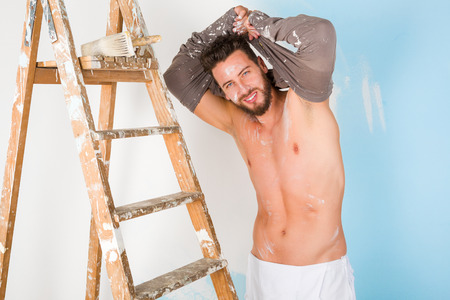 Portrait of handsome sexy paint-splattered painter with vintage ladder, smiling while undressing and looking at camera