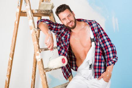 pintor: Retrato del pintor hermoso con la camisa unbottoned, rodillos de pintura y escalera de la vendimia, sonriendo y mirando a la c�mara