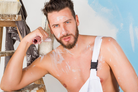 bare chest: Portrait of sexy bare chest paint-splattered painter with paint roller and vintage ladder, looking at camera