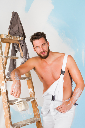 painter: Portrait of seductive bare chest painter with brush and vintage ladder, looking at camera Stock Photo