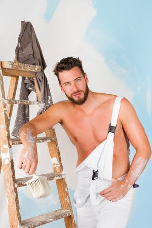 pintor: Retrato de seductor pintor pecho desnudo con pincel y escalera de cosecha, mirando a la c�mara Foto de archivo