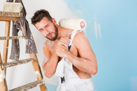 decorating: Portrait of bored bare chest paint-splattered painter with paint roller and vintage ladder, looking at camera Stock Photo