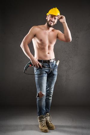 nackte brust: Portrait der attraktiven bärtigen Arbeiter in Jeans und gelben Helm, ohne Hemd, lächelnd und stand mit Bohrer auf einem grauen Hintergrund