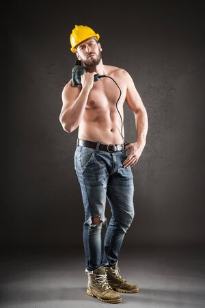 male chest: Portrait of attractive bearded workman in jeans and yellow helmet, shirtless, standing with drill on a gray background Stock Photo