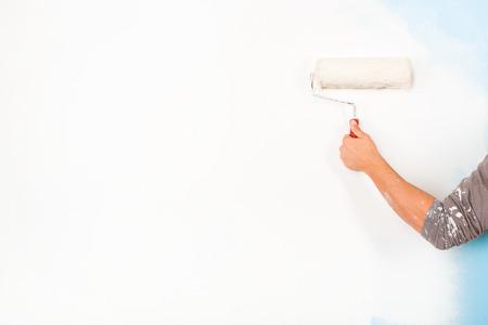 pintor: Cierre de brazo pintor en camisa pintura salpicada pintura de una pared con el rodillo de pintura; espacio de la copia