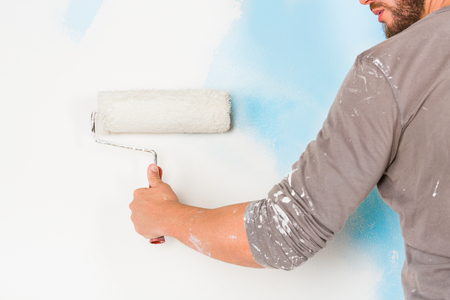painting and decorating: Close up of painter arm in splattered paint shirt painting a wall with paint roller; copy space