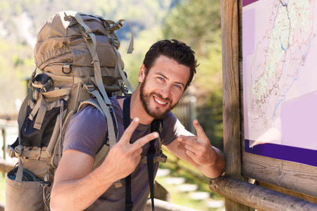 freedom nature: Smiling beard hiker with backpack doing the V sign beside the map panel
