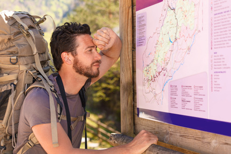 trails: Pensive beard hiker with backpack studying the map