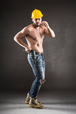 funny bearded man: Portrait of attractive bearded workman in jeans and yellow helmet, shirtless, with drill on a gray background Stock Photo