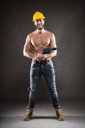 worker man: Portrait of attractive bearded workman in jeans and yellow helmet, shirtless, smiling and standing with drill on a gray background Stock Photo