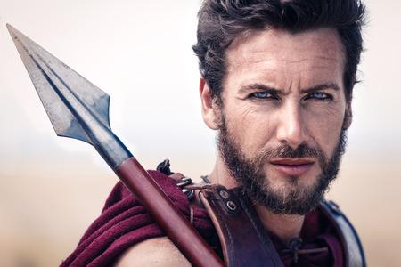 romano: Retrato de guapo y orgulloso antiguo guerrero en armadura con una lanza. Soldado espartano. Paisaje de fondo