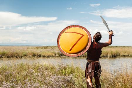 escudo: Retrato de la lucha contra la antigua Warr en armadura con la espada y el escudo. Soldado espartano. Paisaje de fondo