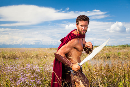 ancient greek: Portrait of ancient shirtless warrior with sword and red cloak. Spartan Soldier. Landscape background
