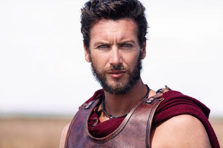 uomo rosso: Ritratto di un antico guerriero bello e fiero in armatura. Soldato Spartan. Sfondo Paesaggio