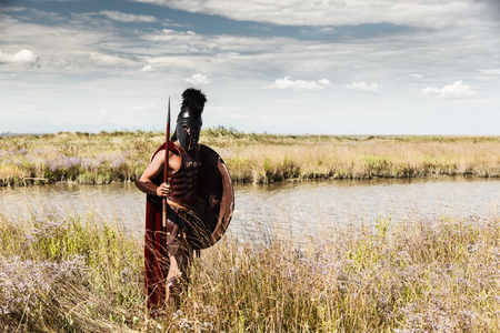 cascos romanos: Retrato de la antigua Warr en armadura con una lanza, escudo y casco. Soldado espartano. Paisaje de fondo