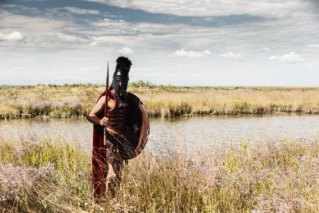 soldati romani: Ritratto di antica Warr in armatura con la lancia, scudo ed elmo. Soldato spartano. sfondo paesaggio Archivio Fotografico