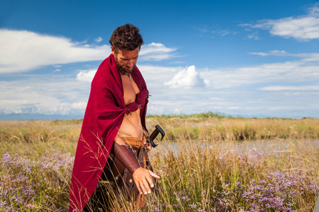 ancient warrior: Portrait of ancient shirtless warrior with sword and red cloak. Spartan Soldier. Landscape background