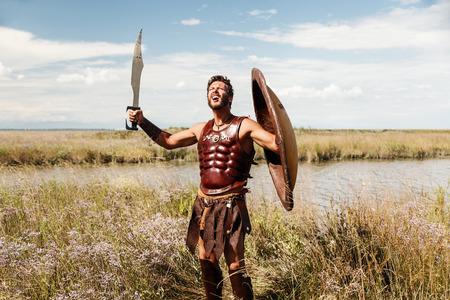 romana: Retrato de la lucha contra el antiguo guerrero en armadura con la espada y el escudo. Soldado espartano. Fondo del paisaje Foto de archivo