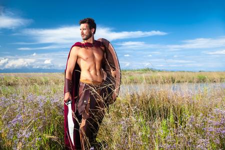 guerrero: Retrato de antiguo guerrero sin camisa con la espada, escudo y capa roja. Soldado espartano. Fondo del paisaje
