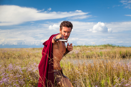 spartan: Portrait of ancient shirtless warrior with sword and red cloak. Spartan Soldier. Landscape background