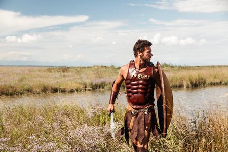 Portrait des Kampfes gegen alten Krieger in Rüstung mit Schwert und Schild. Spartan Soldat. Landschaft Hintergrund Standard-Bild