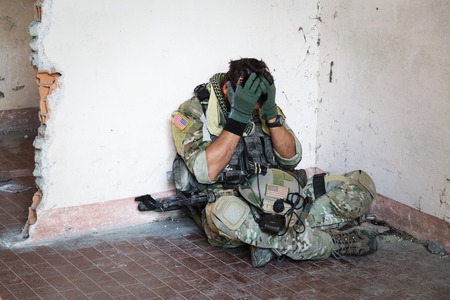 Portrait of Shocked American Soldier Resting from Military Operation; Indoor Ruins Location