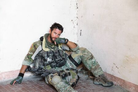 affliction: Portrait of Tired American Soldier Resting from Military Operation; Looking at Camera; Indoor Ruins Location Stock Photo