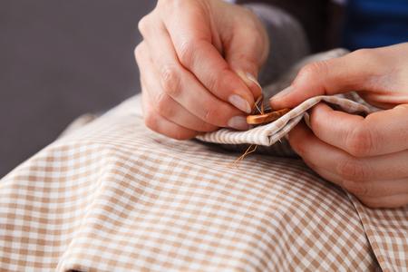 coser: Cierre de costura de botones La mujer da en tela marrón