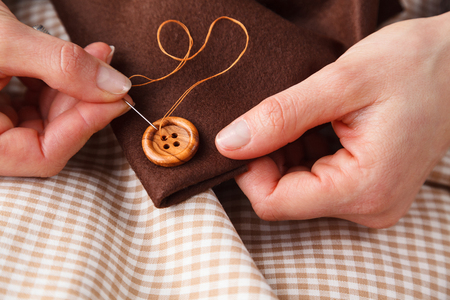 coser: Close up of Woman Hands sewing button on brown fabric