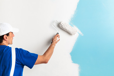 roller: Back view of painter painting a wall with paint roller, with copy space